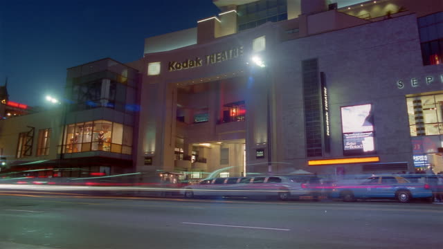 Time lapse wide shot traffic outside Kodak Theatre at night / pan Hollywood & Highland complex / Los Angeles