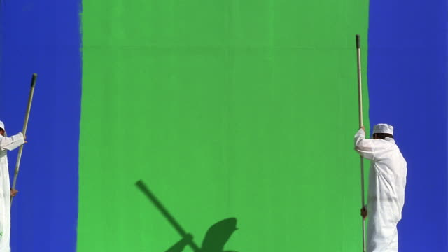 time lapse wide shot two painters painting green wall blue / green screen - wand stock-videos und b-roll-filmmaterial