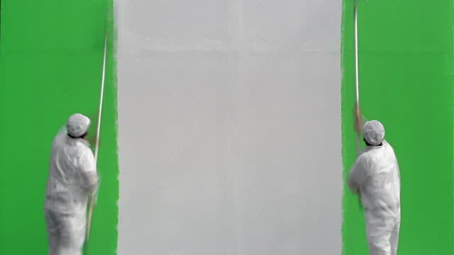 Time lapse wide shot two painters painting white wall green / green screen