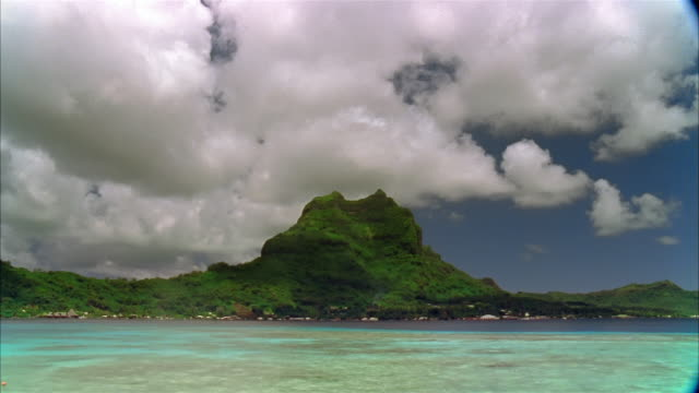 vidéos et rushes de time lapse wide shot view of mount otemanu with big fluffy clouds in background / bora bora - bora bora