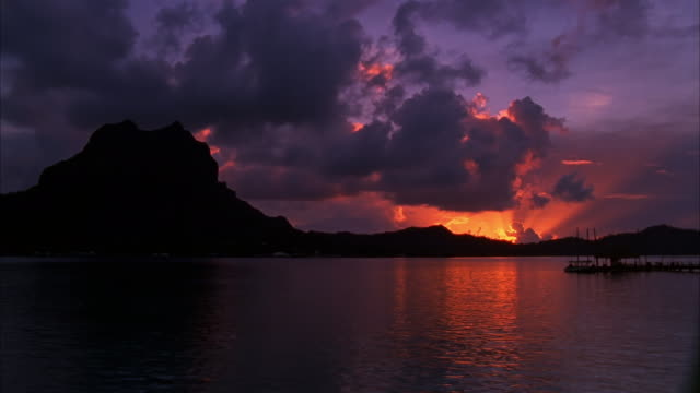 time lapse wide shot view of mount otemanu with big fluffy clouds in background at sunset / bora bora - tropical tree stock videos & royalty-free footage
