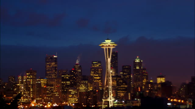 time lapse wide shot view of space needle as day dawns in downtown seattle / washington state - washington mutual tower stock videos & royalty-free footage
