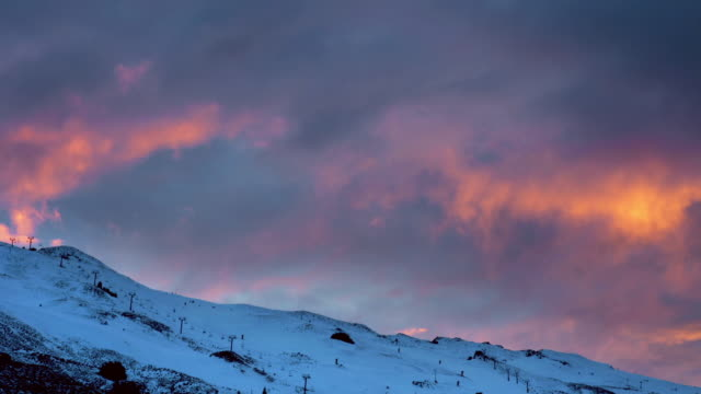 Time lapse wide shot view of sunrise over Coronet Peak skifield near Queenstown / South Island, New Zealand