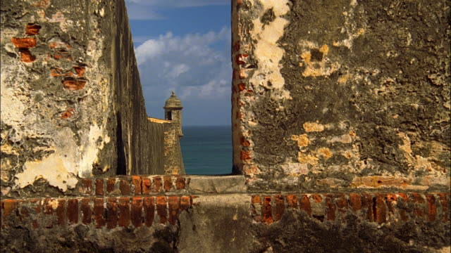 Time lapse wide shot view through walls of El Morro of San Juan Bay and visitors entering lookout tower/ Puerto Rico