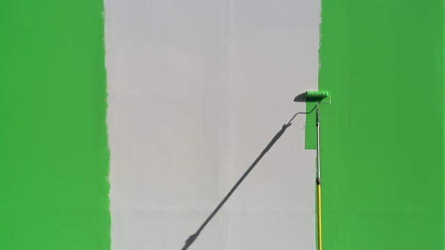 time lapse wide shot white wall being painted green / green screen - paint roller stock videos & royalty-free footage