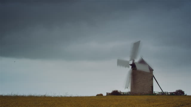 ws, time lapse, wind mill in a cereal field, flowers, cloudy sky - ブルターニュ点の映像素材/bロール