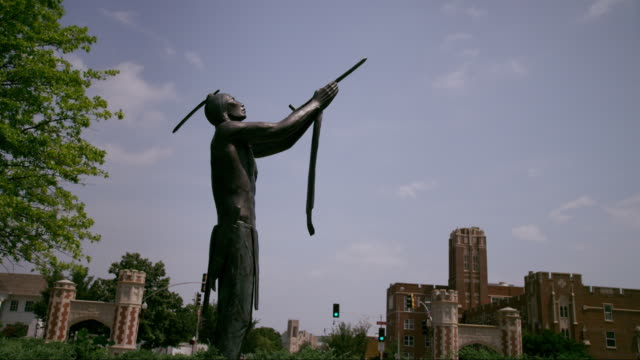 time lapse with blue sky and white clouds, bronze statue of native american holding peace pipe - oklahoma stock-videos und b-roll-filmmaterial