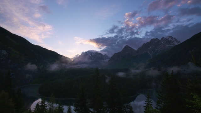 vídeos de stock, filmes e b-roll de time lapse with moving clouds at sunrise with view over lake blindsee to the mountain zugspitze at fernpass. - montanha zugspitze