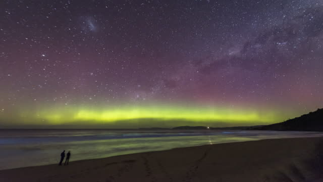time lapse with two people standing on a beach watching the aurora australis or southern lights with bioluminescence in the waves, tasmania. - aurora australis stock videos & royalty-free footage