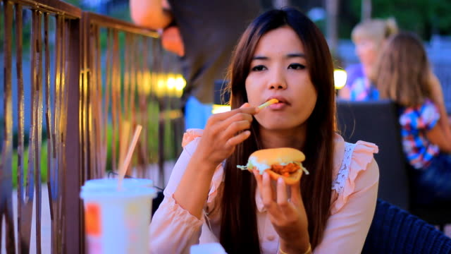 hd-zeitraffer: frau essen burger - fast food stock-videos und b-roll-filmmaterial