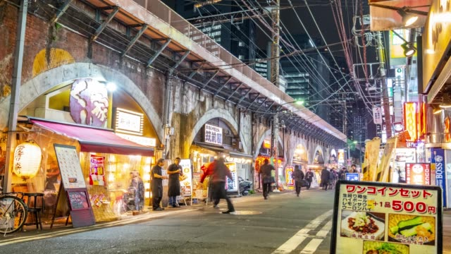4K Time Lapse - Zoom in Crowd walking beside shimbashi station railway shopping and eating - Tokyo Japan