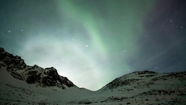 time lapse zoom in of beautiful aurora borealis dancing with starry and clouds on hill at before sunrise - mystery stock videos & royalty-free footage