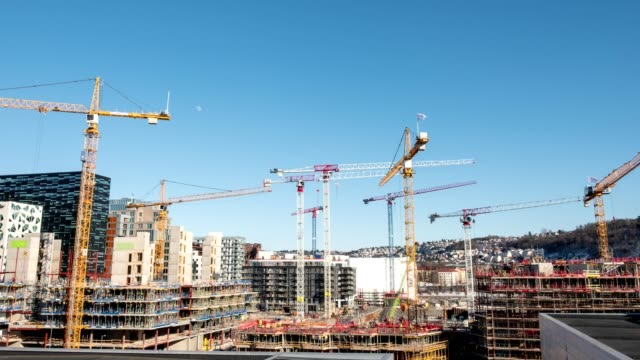 time lapse zoom in of construction building with cranes and derrick and blue sky in the city - construction industry stock videos & royalty-free footage