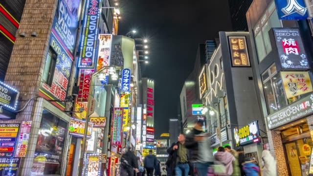 vidéos et rushes de 4k time lapse-zoom arrière vue d'oeil de marche de la foule shopping zone de shinjuku-tokyo japan - panneau de rue
