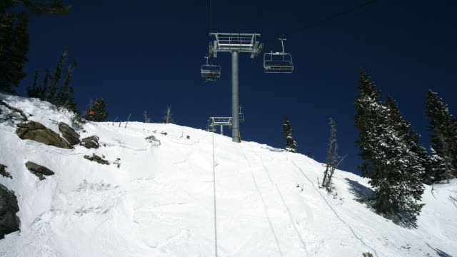 Time lapsed ski lift ride up a snowy mountain