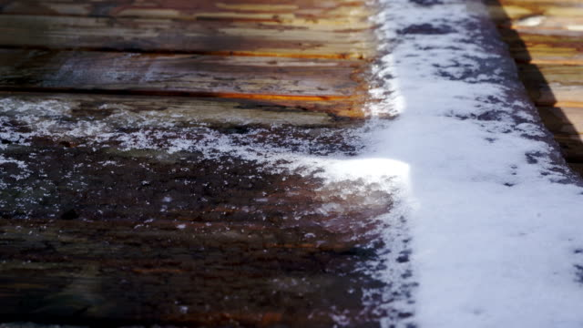 time lapse:the melting of snow - terrazza in legno video stock e b–roll