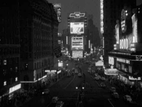 time square w/ buildings around lit signs advertisements traffic moving on broadway 7th avenue crowds of pedestrians people walking nyc midtown 42nd... - broadway manhattan video stock e b–roll