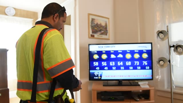a time warner cable inc technician fixes a problem with the cable internet inside the home of a customer in pallisades park new jersey us on friday... - cable box stock videos and b-roll footage