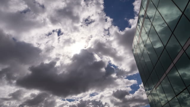 Timelaps of cloudy sunny day with a glass building in the background