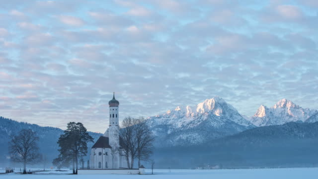 4K timelaps of the Church St. Coloman in morning winter landscape, Schwangau, Germany