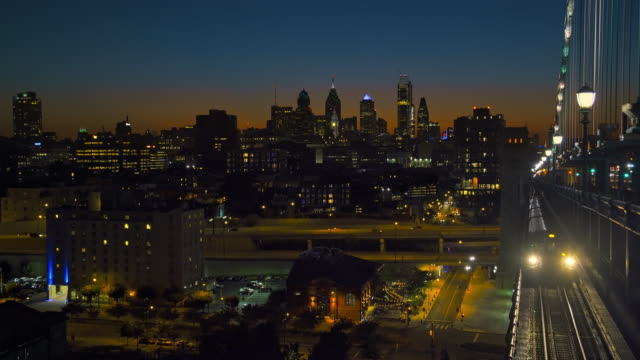 time-laps: philadelphia downtown at sunset. the train approaching on the elevated railroad on the bridge. the view from the benjamin franklin bridge over the piers in old city and delaware river. - philadelphia pennsylvania video stock e b–roll