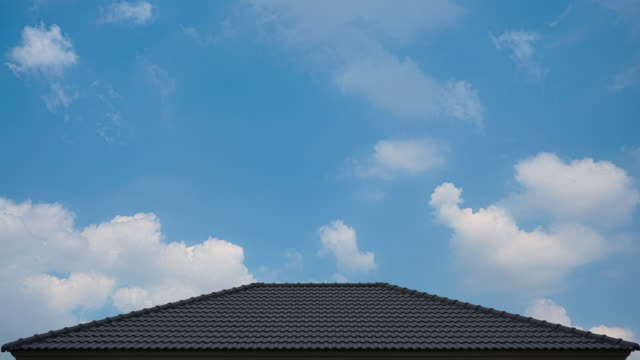 time-lapse 4k roof of construction house with blue sky and cloud background - roof tile stock videos & royalty-free footage