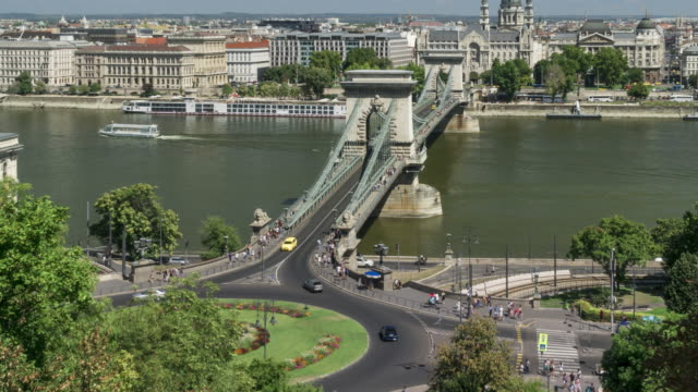 timelapse aerial front view of suspension history bridge and city in budapest, hungary, szechenyi chain bridge at weekend. many transportations, nautical vessel, tour boat along the danube river. concept of travel destination with urban skyline. - chain bridge suspension bridge stock videos & royalty-free footage