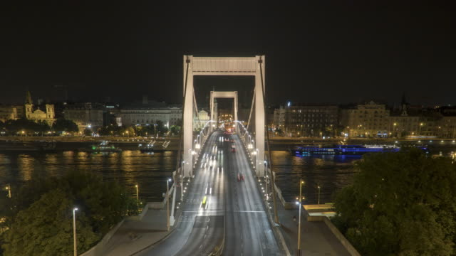 vídeos de stock e filmes b-roll de timelapse aerial high angle front view of suspension history bridge in budapest, hungary, elisabeth bridge at night. many transportations such as car, bus, nautical vessel, tour boat along the danube river. concept of travel destination with urban skyline - ponte széchenyi lánchíd
