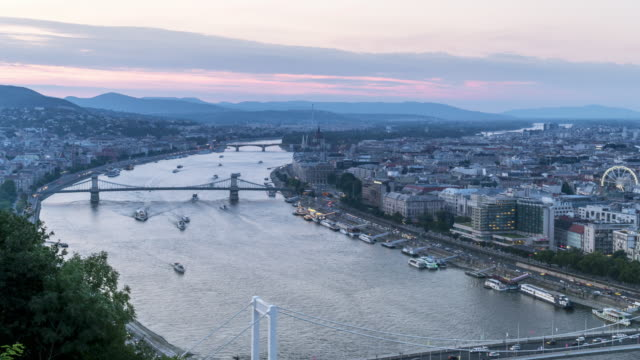 timelapse aerial high angle view of suspension history bridge and city in budapest, hungary, szechenyi chain bridge at twilight. many transportations, nautical vessel, tour boat along the danube river. concept of travel destination with urban skyline. - chain bridge suspension bridge stock videos & royalty-free footage