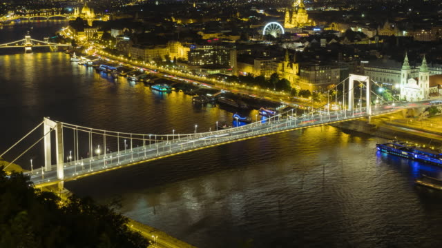 timelapse aerial high angle view of suspension history bridge in budapest, hungary, elisabeth bridge at night. many transportations such as car, bus, nautical vessel, tour boat along the danube river. concept of travel destination with urban skyline. - széchenyi chain bridge stock videos & royalty-free footage