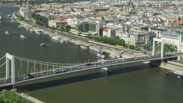 vídeos de stock e filmes b-roll de timelapse aerial high angle view of suspension history bridge in budapest, hungary, elisabeth bridge at weekend. many transportations such as car, bus, nautical vessel, tour boat along the danube river. concept of travel destination with urban skyline. - ponte széchenyi lánchíd