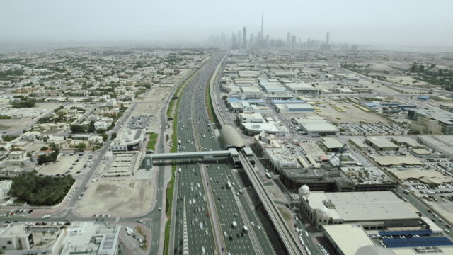 Timelapse aerial shot flying over busy freeway towards the skyscrapers of Downtown Dubai in the United Arab Emirates.