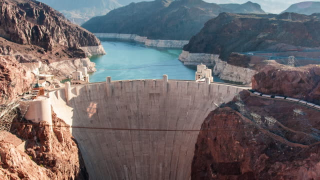 timelapse aerial shot of the hoover dam in nevada with lens flare - dam stock videos and b-roll footage