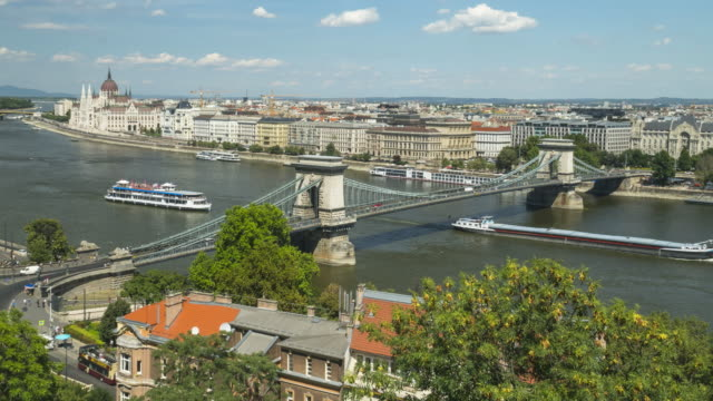 timelapse aerial side view of suspension history bridge and city in budapest, hungary, szechenyi chain bridge at weekend. many transportations, nautical vessel, tour boat along the danube river. concept of travel destination with urban skyline. - chain bridge suspension bridge stock videos & royalty-free footage
