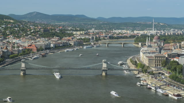 timelapse aerial side view of suspension history bridge and city in budapest, hungary, szechenyi chain bridge at the weekend. many transportations, nautical vessel, tour boat along the danube river. concept of travel destination with urban skyline. - chain bridge suspension bridge stock videos & royalty-free footage
