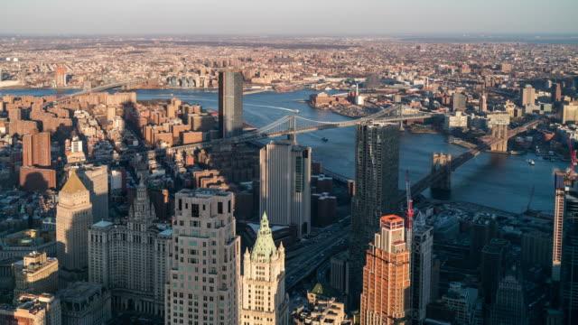 stockvideo's en b-roll-footage met timelapse: aerial vie van brooklyn bridge manhattan bridge en williamsburg bridge, brooklyn new york city zonsondergang - east river