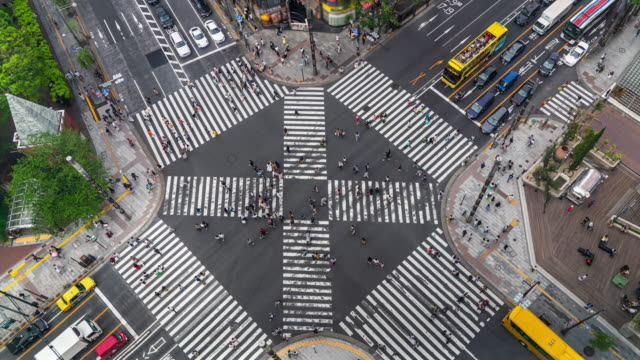 4k timelapse aerial view of crowd people pedestrians and cars crossing intersection road in ginza, tokyo, japan - traffic time lapse stock videos & royalty-free footage