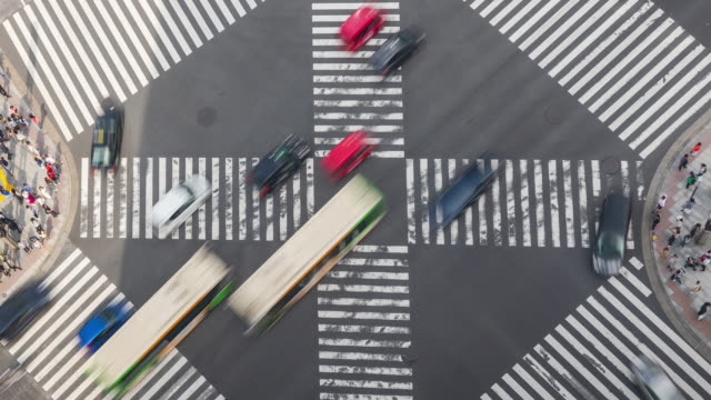 4k time-lapse: aerial view of pedestrians and car crowd at intersection cross-walk ginza crosswalk car traffic on tokyo, japan. zoom out shot - zebra crossing stock videos & royalty-free footage