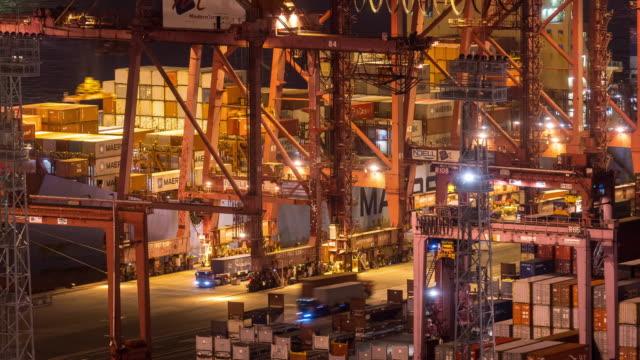 vídeos de stock, filmes e b-roll de lapso de tempo: vista aérea descarregando carga de caminhão de carga de carrinho para navio de carga no porto marítimo de contêineres de hong kong tsing yi à noite - porto comercial