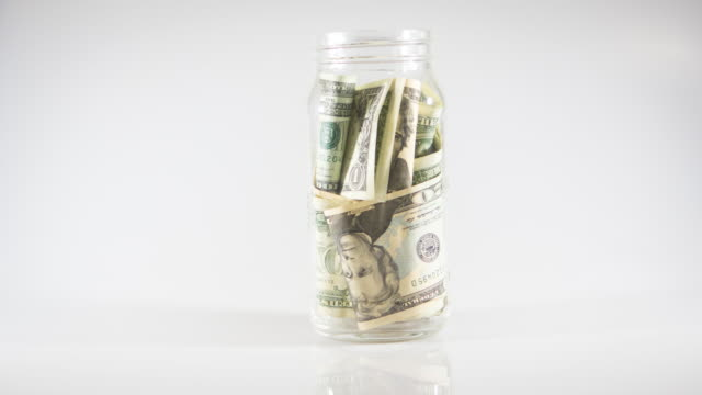 timelapse american dollar 100 into a glass jar for storage - savings stock videos & royalty-free footage