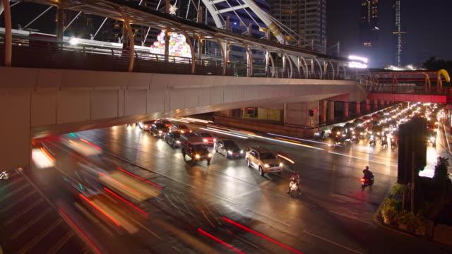 vidéos et rushes de time-lapse et incliner vers le haut: trafic de bangkok en nocturne à arbre non constant. - train aérien
