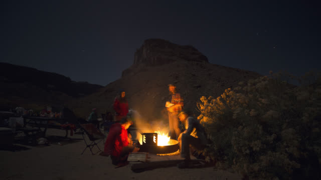 Timelapse as group of friends walk around scenic Moab camp site and sit by fire pit at night.