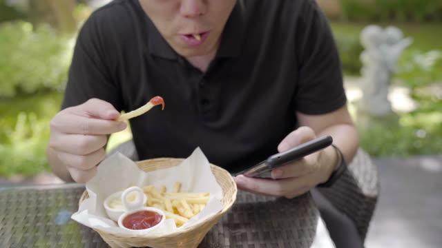 タイムラプス - ファーストフード、不健康なスナックの食事を食べるアジアの男性。携帯電話の再生中にケチャップに浸るフライドポテトチップス - unhealthy eating点の映像素材/bロール