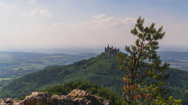 T/L Timelapse at Castle Hohenzollern in Germany. A dolly slider shot revealing the Castle from behind a tree