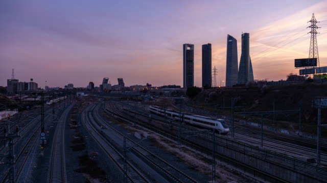 Time-lapse at dusk of the iconic Four Towers Business centre and busy railway