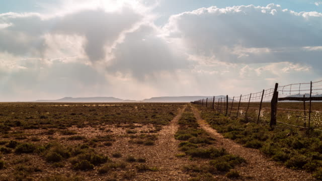 vidéos et rushes de timelapse at sunset of a karoo farm landscape with  a fence and dirt road leading you towards the distant mountains and hills - karoo