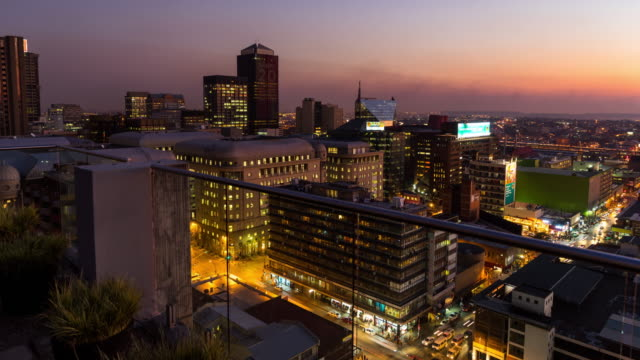 vídeos de stock e filmes b-roll de timelapse at sunset showing the view from a rooftop across new town and the city centre of johannesburg during peak traffic - joanesburgo