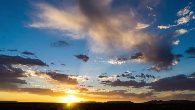 Timelapse at sunset with a dramatic cloudy sky and contrast blue and orange glow as the shot dips to black