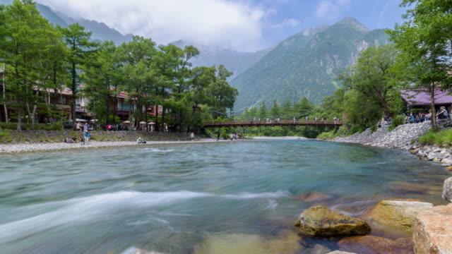 vídeos de stock, filmes e b-roll de 4 k timelapse: rio de azusa com montanha hotaka e kappa-bashi bridge - nagano