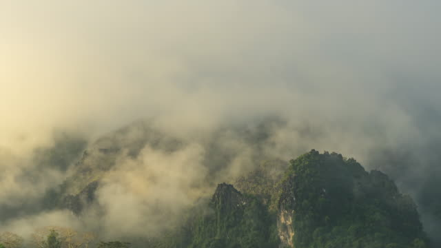 4k time-lapse : beautiful fog moving in sunrise at viewpoint in vang vieng, laos. - laos stock videos & royalty-free footage
